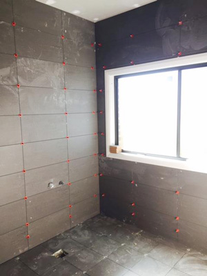 ATR Tile Leveling system in use on large format wall tiles laid in a grid pattern